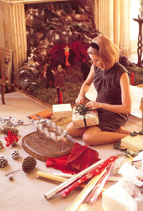 Grace Kelly wrapping Christmas presents in the palace bedroom.: