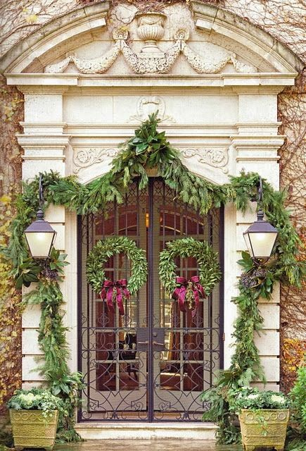 Double wreath at front door with Christmas garlands at formal French chateau