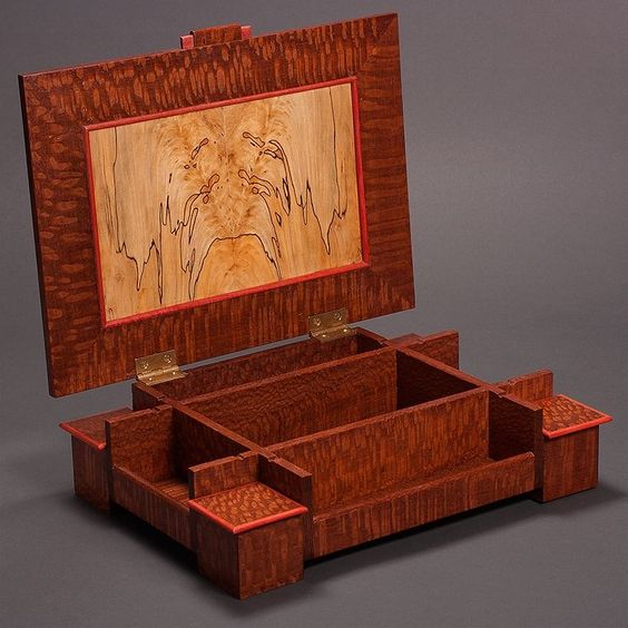 """A keepsake or jewelry box, made of lacewood and spalted maple with pink ivory accents. Nine compartments of different sizes. Five have black suede bottoms. Dimensions: 12"""" x 8-1/2"""" x 3"""""""