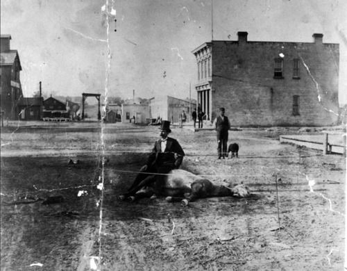 Speculation abounds over the origin and nature of a strange vintage photo from Sheboygan, WI of a man in a top hat apparently sitting on a dead horse in the middle of the street.