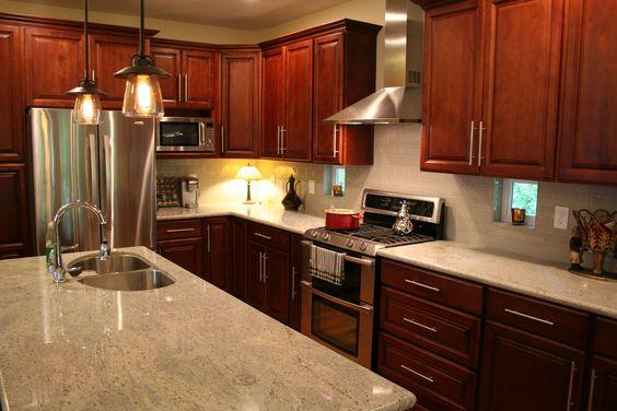 I LOVE my kitchen- Dark cherry cabinets, cashmere granite, pumice subway tile back splash, peekaboo windows, double oven, and old fashioned filament lights.