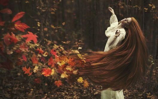Девушка взмахивает длинными рыжими волосами, из которых разлетаются осенние листья: