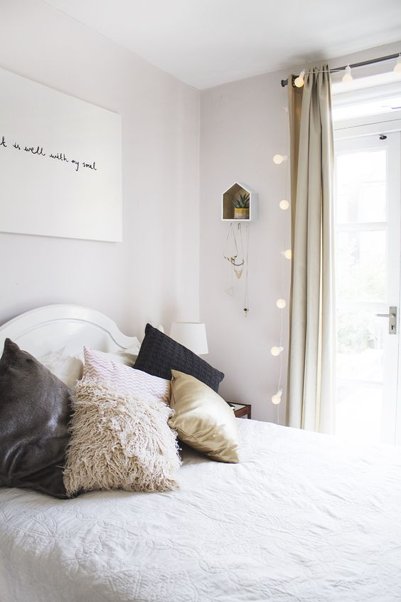 What a pretty pastel room. The framed plant the festoon lights hanging from the curtain rail give it such a cosy feel!: