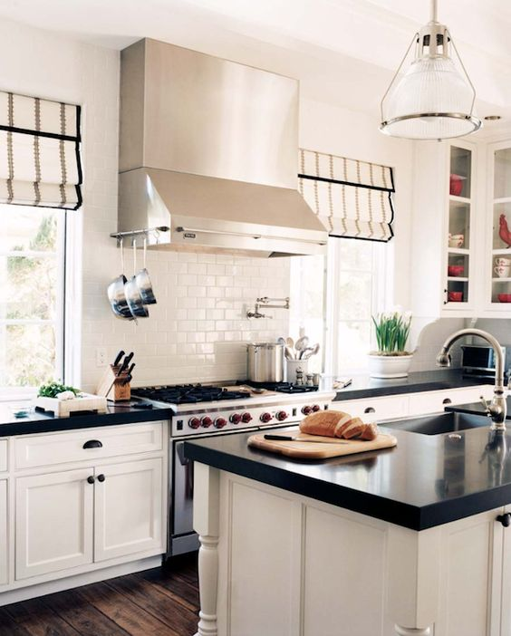 White & black contemporary kitchen design with white kitchen cabinets, black counter tops, white subway tiles backsplash, pot filler, silk white gray striped roman shades, glass-front cabinets, rustic wood floors