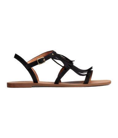 Sandalen aus Velourslederimitat mit Fransen und kleinen runden Nieten oben. Riemen mit Metallschnalle an der Seite. Innensohle aus Lederimitat. Gummisohle.