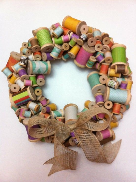 wooden spools wrapped with paper and repurposed into wreath