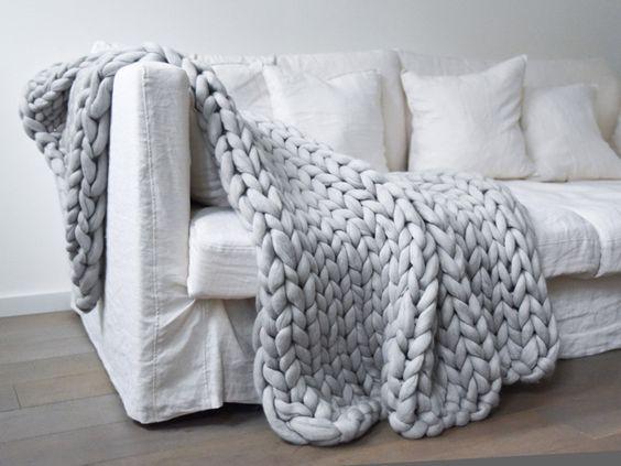 Plaid à grosses mailles gris posé sur un canapé blanc
