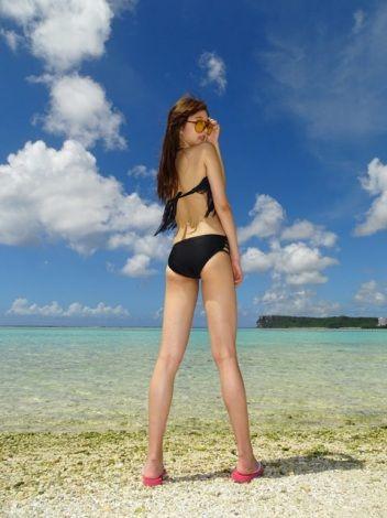 黒いビキニを着てビーチに立って振り返る熊江琉唯の画像