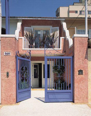 Fachada de casa rosa envelhecido com portão azul, ficou muito charmosa. Uma aposta interessante para fachada de uma casa pequena, estreita...: