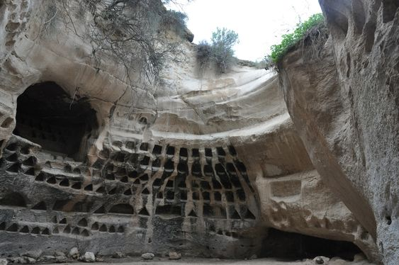 Cut out of the soft limestone is a bell cave with square and triangular niches carved in the walls that was used as a columbarium (dovecote)