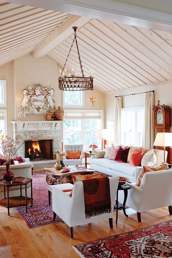 Warm reds and oranges in Sarah Richardson's farmhouse living room with wood on pitched ceiling. #livingroom #farmhouse #sarahrichardson #red