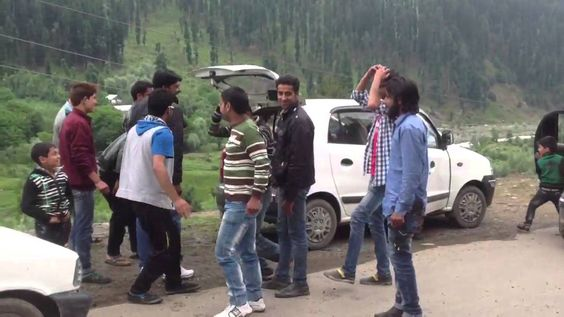 Kashmiri young Muslim boys performing some dance steps on road side..rea...