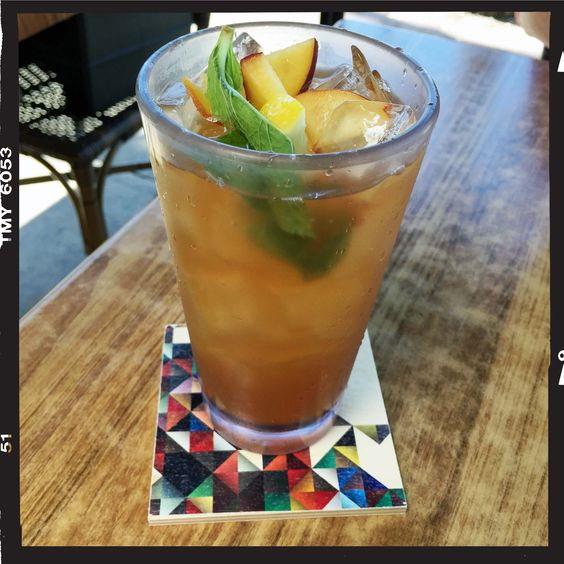 Take your peach iced tea to the next level by adding some peach slices and mint! It's delicious. Photo featuring the Flox 'Prism' Wood Coasters.