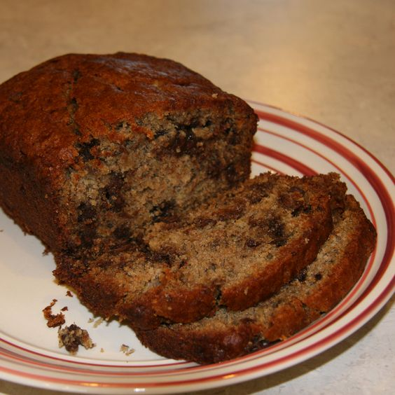 Cinnamon Chocolate Chip Banana Bread    3/4 cup sugar  1 1/2 cups of mashed bananas (about 3 large)  3/4 cup of vegetable oil  2 eggs  2 teaspoons vanilla    2 cups of all-purpose flour (I used 1/2 white and 1/2 whole wheat flour)  1 teaspoon baking soda  1/2 teaspoon baking powder  1/2 teaspoon salt (I probably don't use that much, just a few turns of the sea salt grinder)  1 1/2 teaspoons ground cinnamon    1/2 bag (or about 1 cup) chocolate chips    Preheat oven to 325.  Grease loaf pan…