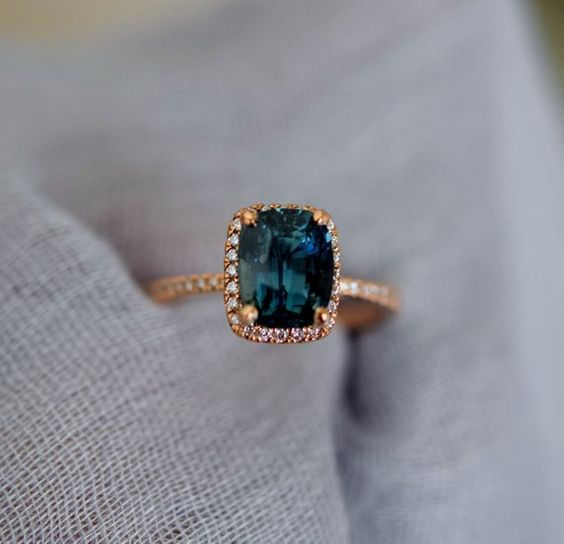Teal sapphire Rose gold engagement ring. Engagement ring by Eidelprecious. This ring features a 3.8ct cushion sapphire. The color is gorgeous deep peacock green with blue flashes. The sapphire is very beautiful and clean. This beauty is set in Eidelprecious signature 14k rose gold
