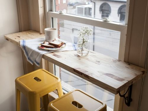 7 Genius Ways to Design a Small Space- long table in front of window with yellow stools. So sweet.