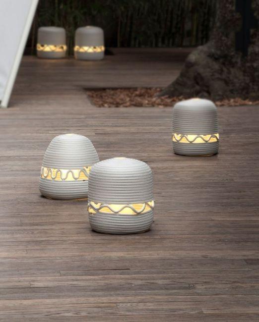 Design: Paola Lenti  Design buitenverlichting, lantaarns. Serie van vloer en tafellantaarns, met vervangbare hoes, gemaakt van ROPE touw in een spiraalvormig patroon. De verlichting is dimbaar en werk via een batterij, ontworpen om ca. 6 uur licht af te geven. De batterij kan opgeladen worden d.m.v. de oplader of ieder andere apparaat met een USB-aansluiting.
