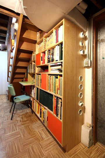 I like the holes in the side of the bookshelves for rolled storage to tuck in behind books sitting forward on the shelf.