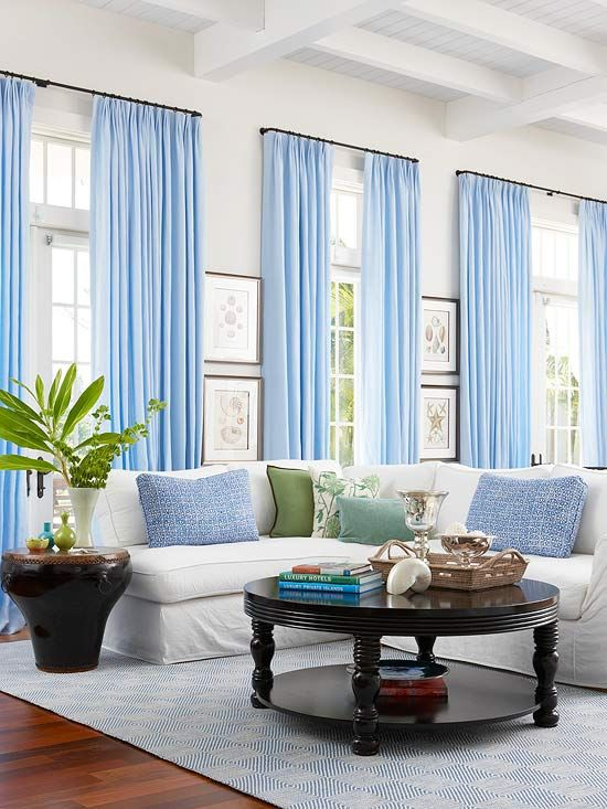 Contrast all-white walls with bright accents. How pretty are these blue curtains?