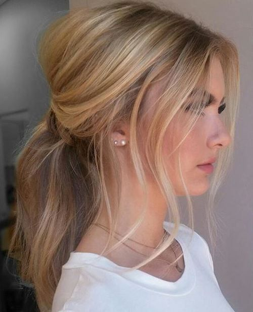 Sweep hair into a low ponytail and let pieces fall out on the sides. Tug sections at the top to create a small bump, and you are good to go with this free style.
