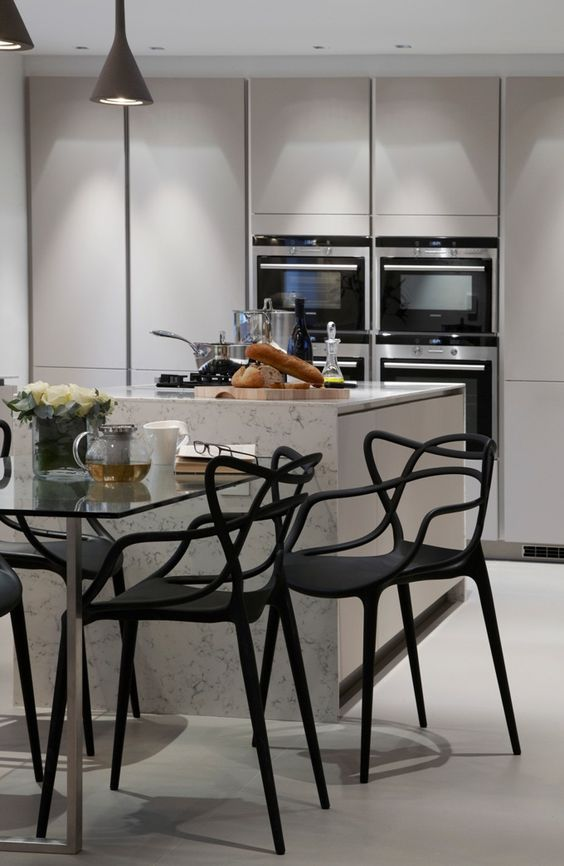 white contemporary kitchen with marble waterfall counter edge with attached gass top dining area and phillippe starck chairs -by Boscolo