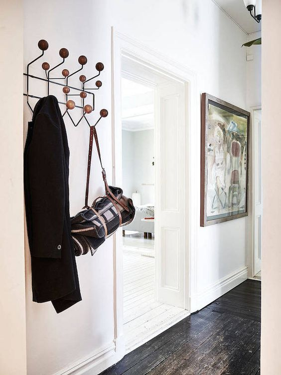 Hallway with black floors and hang-it-all in a calm Swedish home. Stadshem.: