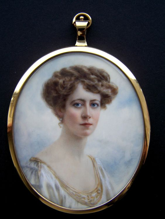 A young Edwardian lady wearing a white dress with gold trim,  with very fashionable upswept hair style of the time period - c1910. Watercolour on natural panel.  Oval, 72mm high. Hallmarked silver frame, London 1910.: