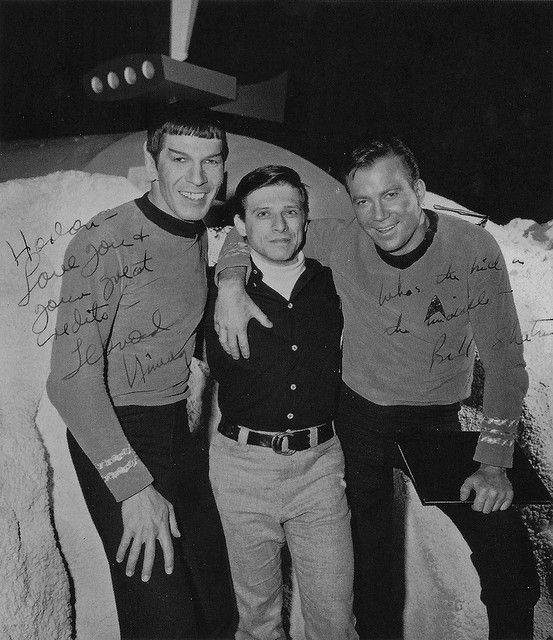 An entertaining autographed shot from 1966 of Leonard Nimoy, William Shatner, both in costume, and Harlan Ellison between them, the science fiction author who wrote the original version of the TOS script The City on the Edge of Forever. In the background are some typical TOS planet rocks and the hut that was used in the filming of Mudd's Women.
