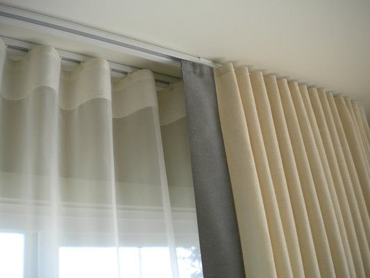 Three rods, ceiling mounted. This page has a great overview of formal vs. casual and ideas for types of drapery. This is an example of ripplefold.