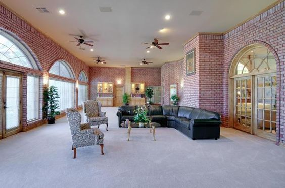 Big, bright sunroom with brick and lots of windows.