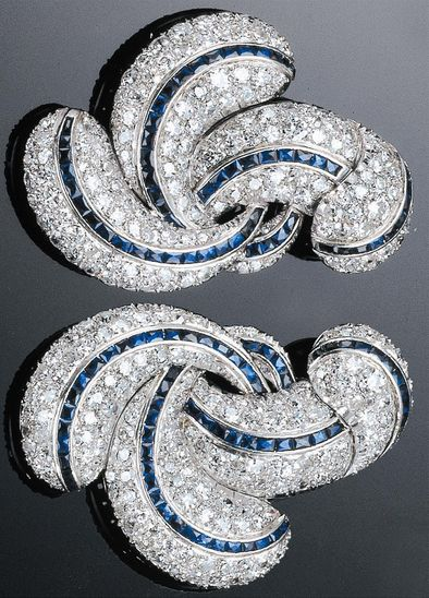 PAIR OF PLATINUM, GOLD, DIAMOND AND SAPPHIRE CLIPS, 1930'S. Designed as swirls of pavé diamonds with a line of sapphires running through each swirl.