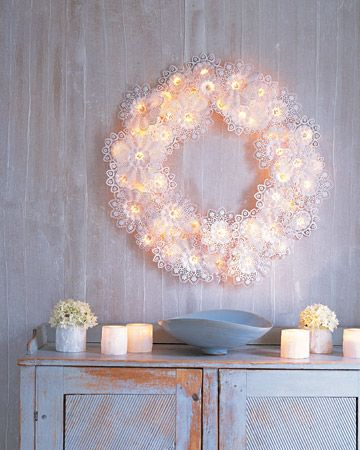 "A delicate-looking wreath that creates the magical effect of candles flickering in the snow is easy to make and surprisingly sturdy. Wreath frames are strung with twinkling lights that are nestled in frothy, doilylike paper bouquet holders known as ""Biedermeiermanschetten.""    Read more at Marthastewart.com: Paper-Doily Wreath - Martha Stewart Crafts"