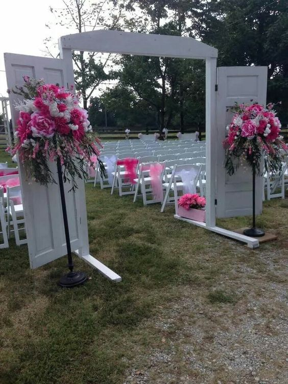 These flower arrangements for my niece's wedding were done on old floor lamps and the old doors were mounted and used as an entrance to the outdoor ceremony.