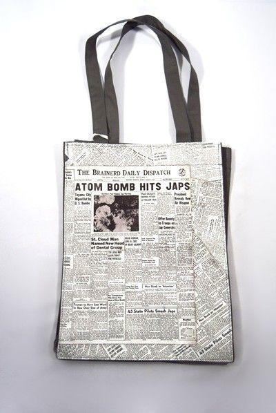 """Bolso Atom Dogo de color gris oscuro y blanco. Diseño con estampado """"Atom Bomb"""", dos asas medianas, bolsillo interno con cierre de cremallera y detalle de mosquetón."""