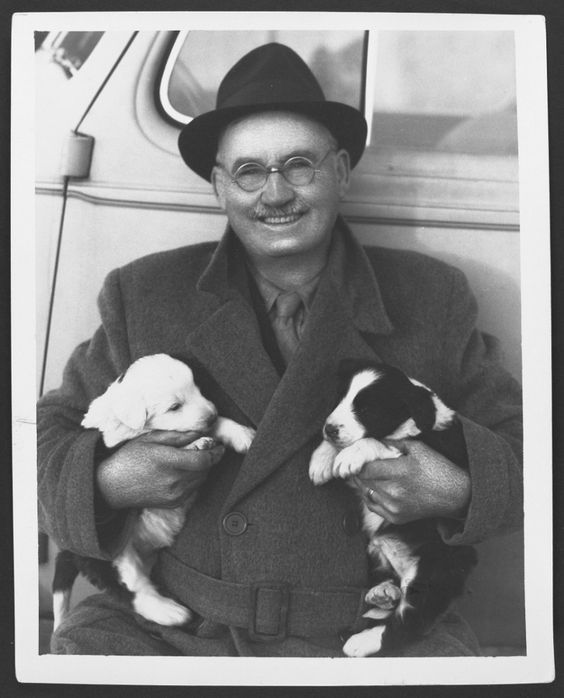 Photograph of Dr. James Naismith with two puppies during a trip to Canada…