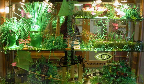 """Premier Optical spring Window Displays pring Window Display 2009  We spray painted and reused the mannequin heads from the Winter 2008 window and spent a month of weekends and evenings curling thousands of green pipe cleaners into """"springs"""". We also made """"spring bouquets, and hair for the figures from the coiled chenille. I"""