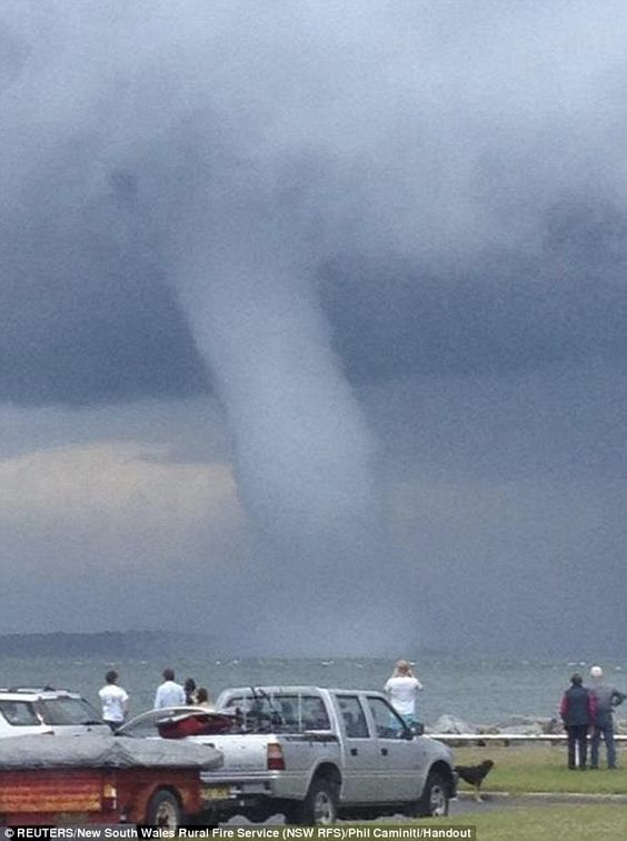 Too close for comfort: People look at the waterspout near to the shoreline at Batemans Bay, New South Wales, Australia.