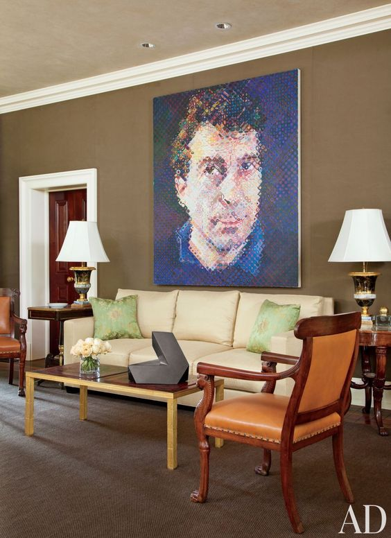 Designer Thomas Jayne convinced a Philadelphia-area couple to line their living room walls in a chocolate-brown Holland & Sherry cotton, providing a distinctive backdrop for the large Chuck Close portrait Bill and other artworks, including a tabletop sculpture by Tony Smith; the sofa is upholstered in a Rogers & Goffigon fabric, and the pillows are covered in a Clarence House silk.  ARCHITECT: n/a DESIGNER: Jayne Design Studio Inc. PHOTOGRAPHER: Roger Davies