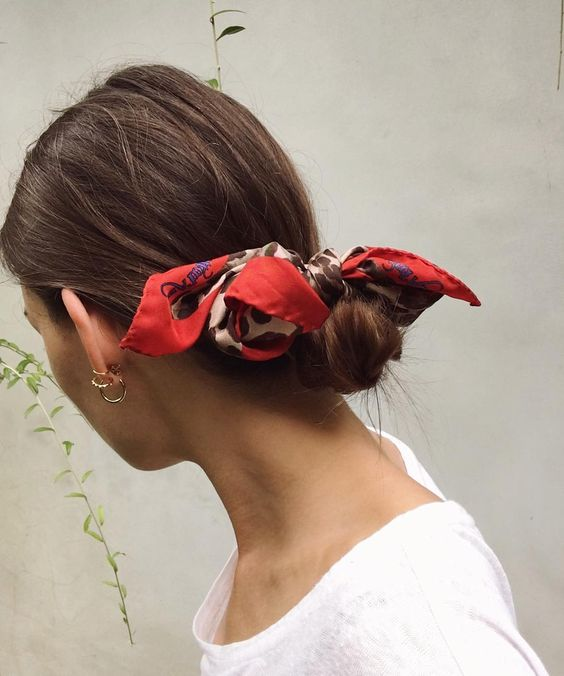 Small low hair bun with red scarf tied around it.