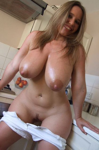 Une femme cougar presque nue dans sa cuisine