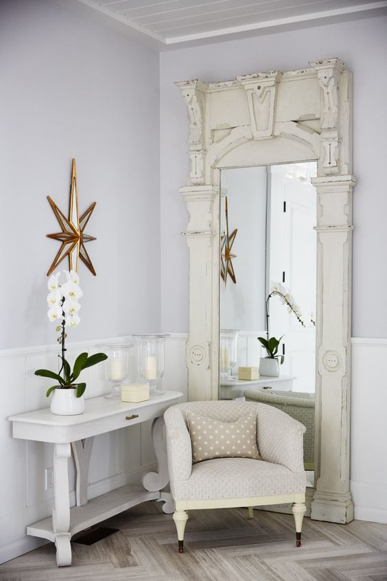Vintage floor mirror, chubby club chair, and white console table in a modern country foyer in Sarah off the Grid. #SarahRichardson #entryway #foyer
