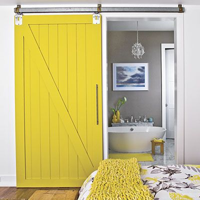 Cool for bath or laundry room door.   A standard swinging door can take a lot of floor space in your bath, but a sliding door is convenient and compact. A modern barn door slides along a track to close off this bath. The bright saffron color ties in with the saffron-and-gray bedding and updates the look. [for connecting master bed and bath]