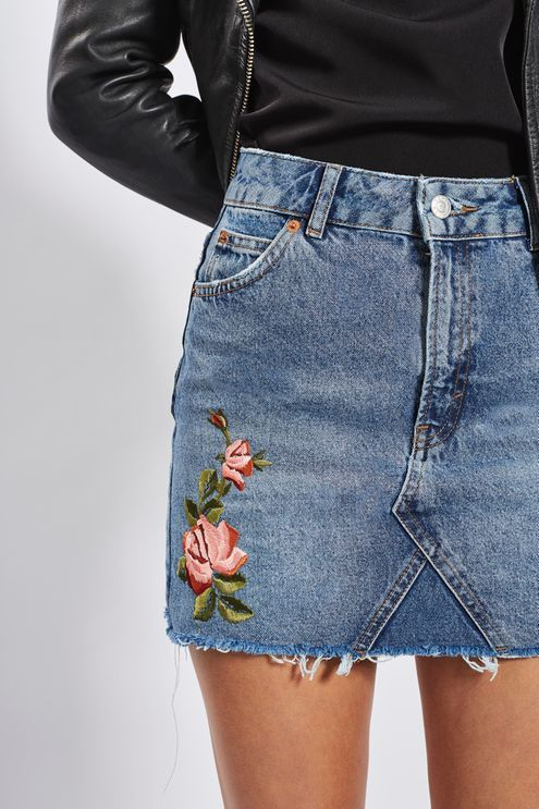 Update the denim skirt in this unique style. In a mid stone blue, it comes in a mini cut, detailed with pretty floral rose embroidery and is finished with a frayed hem. #Topshop: