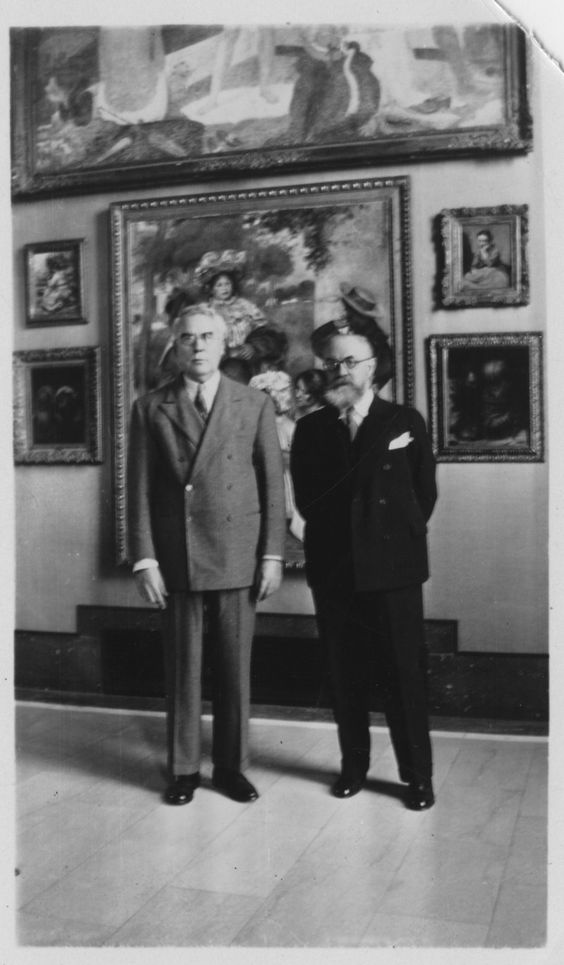 "HENRI MATISSE and DR. ALBERT BARNES c. 1930 before Pierre-Auguste Renoirs painting of ""The Artists Family"" (1896) in the Barnes Foundations Main Gallery..."
