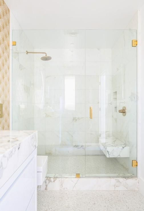 A gold handle accents a seamless glass shower door opening to a seamless glass shower fitted with a marble floating bench fixed against marble surround tiles and over a mosaic marble floor.