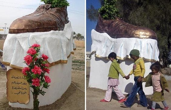 Children walk past a sculpture of a shoe in Tikrit, Iraq, a monument to the shoe which was thrown at then-President George W Bush when he visited the country