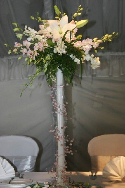 A Beach Inspired Wedding Centerpiece Features A White Eiffel Tower Vase Wrapped In Pink And