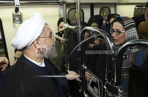 "In this photo released by the official website of the office of the Iranian Presidency, Iran's President Hassan Rouhani listens to a woman (separated from men) while boarding a subway in Tehran, Iran, Monday, Jan. 19, 2015. Some Iranian top officials Monday went to work using subway and other public transportation systems showing their support for ""National Air Clean Day."" (AP Photo/Iranian Presidency Office, Mohammad Berno)"