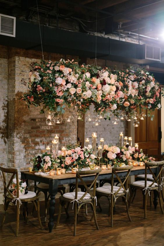 These rustic tables were adorned with lush pink floral pieces + below one stunning hanging floral arrangement | Image by Greer Gattuso Photography