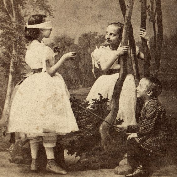 Children at play. Date and origin unknown. No cleanup of scratches/spots.I don't really get this game. Blindfold one girl and then jab at her with a stick? This does not seem like a game children should be playing.